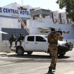 A Somali government soldier walks outside the Central Hotel after a suicide attack in Mogadishu