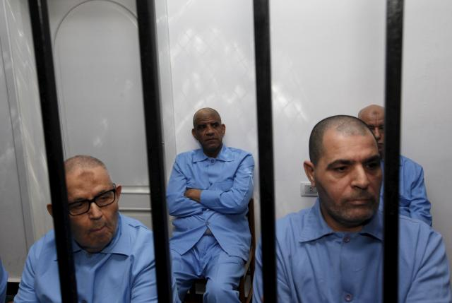 Former intelligence chief of Gaddafi's regime Abdullah al-Senussisi (C) and other Gaddafi regime officials sit behind bars during a verdict hearing at a courtroom in Tripoli, Libya July 28, 2015. REUTERS/Ismail Zitouny