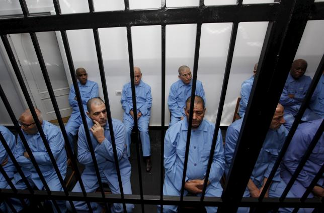 Former intelligence chief of Gaddafi's regime, Abdullah al-Senussisi (2nd row L), and other Gaddafi regime officials sit behind bars during a verdict hearing at a courtroom in Tripoli, Libya July 28, 2015. REUTERS/Ismail Zitouny
