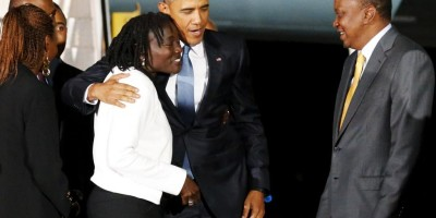 U.S. President Barack Obama embraces his half-sister Auma Obama and is greeted by Kenya's President Uhuru Kenyatta as he arrives at Jomo Kenyatta International Airport in Nairobi
